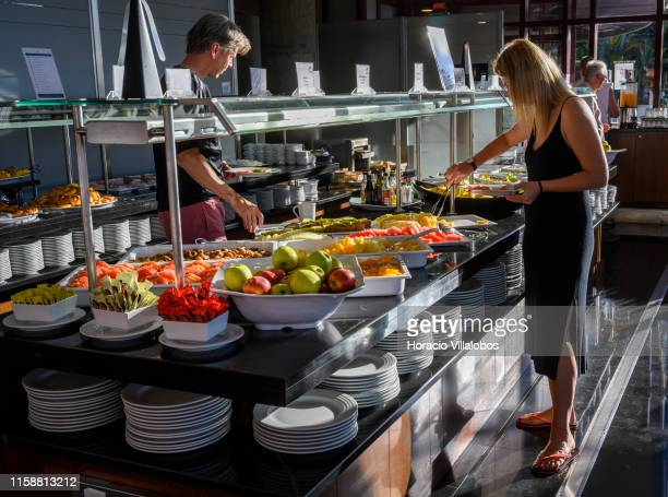 Guests help themselves at the breakfast buffet at one of the restaurants in fivestar Pestana Casino Park hotel on June 26 2019 in Funchal Portugal...