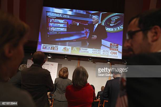 Guests in the early hours watch live coverage on CNN that shows initial projections for voting results in Florida at the US elections party hosted by...