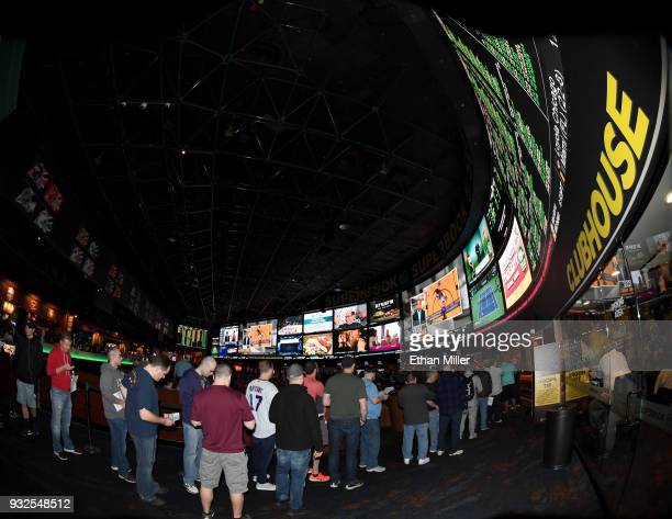 Guests line up to place bets as they attend a viewing party for the NCAA Men's College Basketball Tournament inside the 25000squarefoot Race Sports...