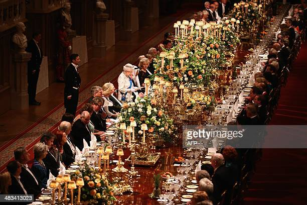 Guests listen during a speech by Britain's Queen Elizabeth II in honour of the President of Ireland Michael D. Higgins at the State Banquet during...