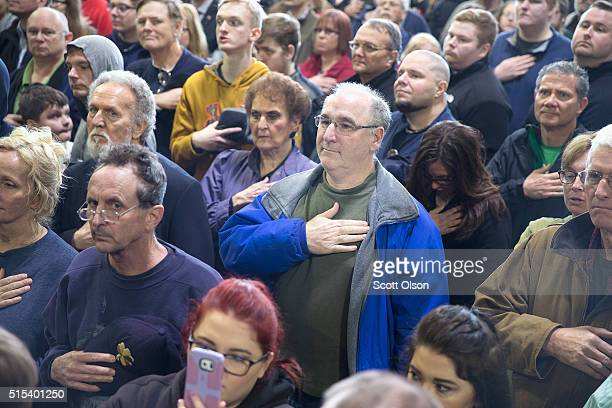 Guests listen to the national anthem before the start of a rally with Republican presidential candidate Donald Trump at the Central Illinois Regional...