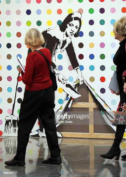 Guests look at a painting by Banksy on display during a press preview of the Auction to fight AIDS in Africa, at the Gagosian Gallery on February 4,...