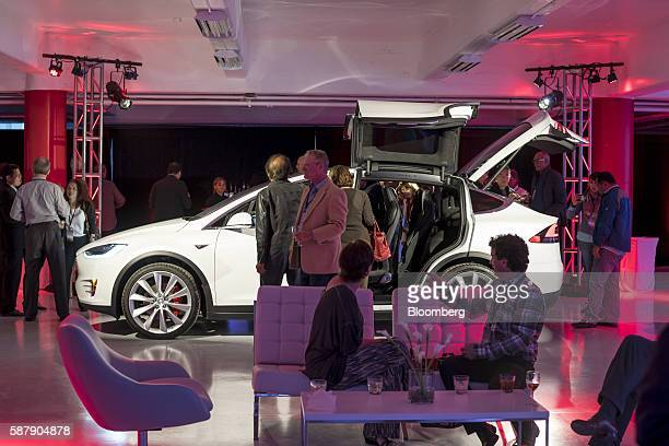 Guests look at a Tesla Motors Inc Model X electric vehicle on display at the company's new showroom in San Francisco California US on Tuesday Aug 9...