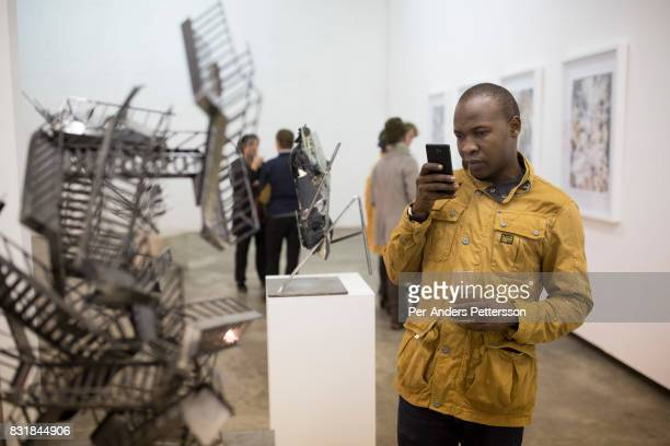 Guests look at an art exhibition at an opening at Hazard Gallery in Maboneng district on March 17 2016 in downtown Johannesburg South Africa A former...