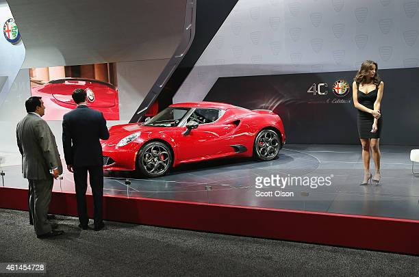 Guests look over the new Alfa Romeo 4C coupe during the media preview at the North American International Auto Show on January 12 2015 in Detroit...