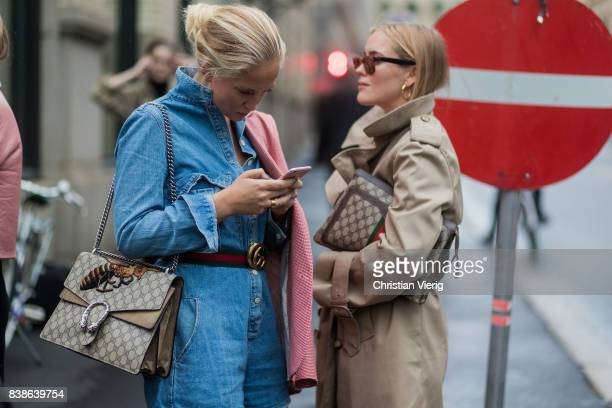 Guests looking at a phone wearing Gucci bag trench coat denim dress outside Bik Bok Runway Award on August 24 2017 in Oslo Norway