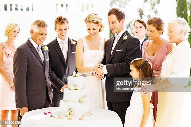 Gli ospiti alla ricerca di sposa e sposo taglio Torta durante la ricezione