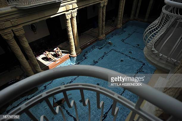 Guests lounge on the deck of an indoor pool at the Gellert bath on August 11 in Budapest The sumptuously renovated Art Nouveau complex which includes...