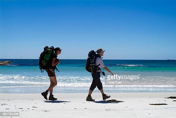 Guests of Cradle Mountain Huts walk along a remote beach on the Bay of Fires walk a fourday hike that traverses Tasmania's far northeast coastline...