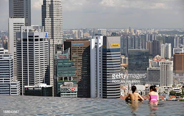 Guests of the Marina Bay Sands hotel in Singapore look over the citystate's financial district from a rooftop swimming pool on May 13 2013...