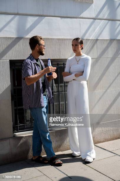 Guests outside MFPEN guy wearing jeans and striped shirt and a girl with white wide pants and white long sleeves top during Copenhagen fashion week...