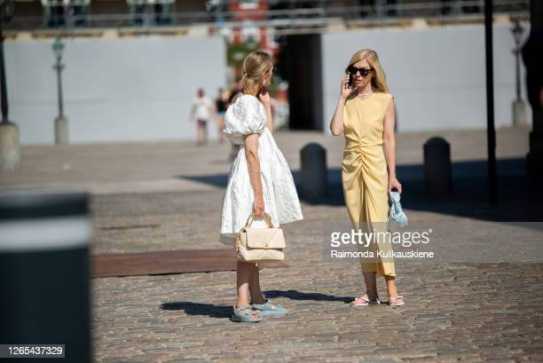 Guests outside Remain Birger Christensen wearing white and yellow dresses during Copenhagen fashion week SS21 on August 11, 2020 in Copenhagen,...