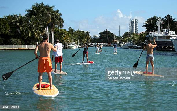 Guests paddleboard following the Dedon Breakfast at AD Oasis at James Royal Palm Hotel on December 7 2013 in Miami Beach Florida