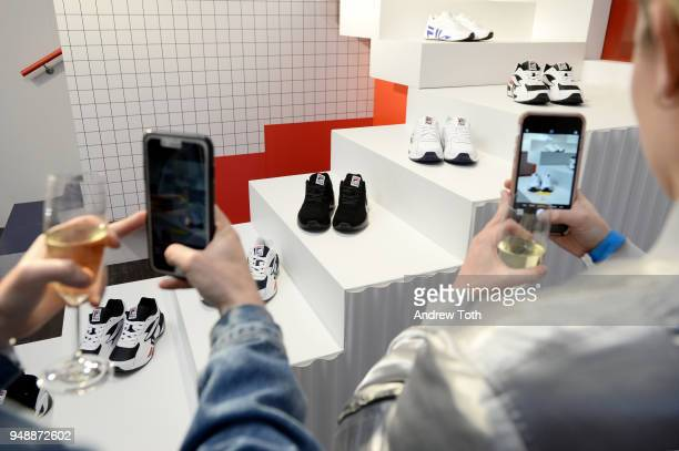 Guests photograph sneakers on display at the Launch of the FILA Mindblower PopUp Powered by Ciroc on April 19 2018 in New York City