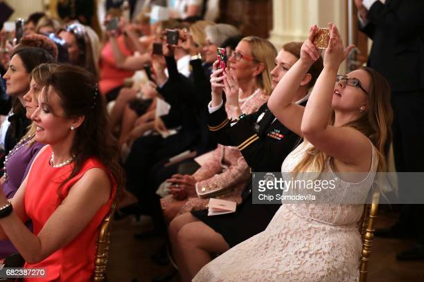Guests photograph US President Donald Trump and first lady Melania Trump during an event for military mothers on National Military Spouse...