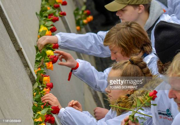 Guests place flowers at the Wall Memorial during the central commemoration ceremony for the 30th anniversary of the fall of the Berlin Wall, on...