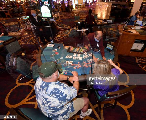 Guests play blackjack at a table installed with plexiglass safety shield dividers and only three seats for social distancing at Mandalay Bay Resort...