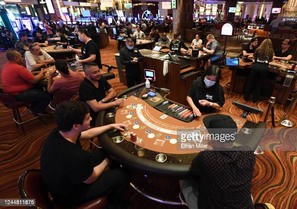 Guests play blackjack at tables with only three players allowed at a time at the Red Rock Resort after the property opened for the first time since...