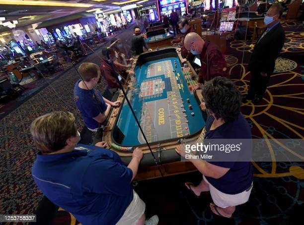 Guests play craps at Mandalay Bay Resort and Casino after the Las Vegas Strip property opened for the first time since being closed in midMarch...