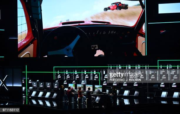 Guests play the game 'Forza Horizon 4' on stage at the Xbox 2018 E3 briefing in Los Angeles California on June 10 2018 ahead of the 24th Electronic...