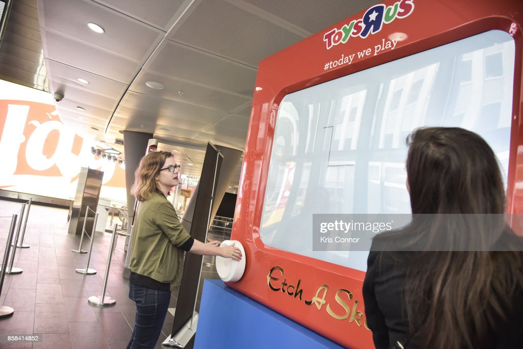 Guests play with a giant Etch A Sketch during the 'Toys 'R' Us Takes Over Fulton Street Subway Station with Giant Etch A Sketch,' event at Fulton Center on October 6, 2017 in New York City.
