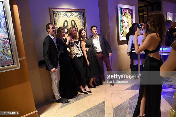 Guests pose for a photo at the Underwater Dreams To Life In Color Art Exhibit Featuring Antonio Dominguez De Haro And Romero Britto At Four Seasons...