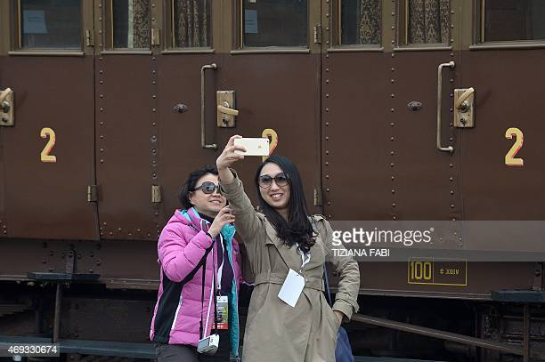 Guests pose for a selfie near the Tuscany's touristic train at the Torrenieri Montalcino station on April 11 2015 near Montalcino Italian Culture...