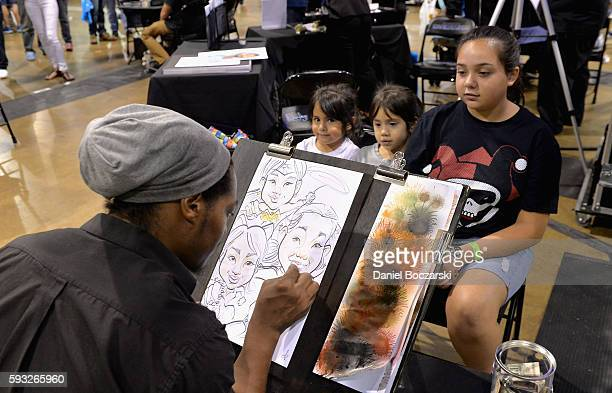 Guests pose for a sketch during Wizard World Comic Con Chicago 2016 Day 4 at Donald E Stephens Convention Center on August 21 2016 in Rosemont...