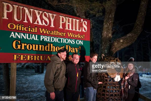 Guests pose for photos at the site of the Groundhog Day ceremonies hours before sunrise on February 2 2018 in Punxsutawney Pennsylvania Punxsutawney...