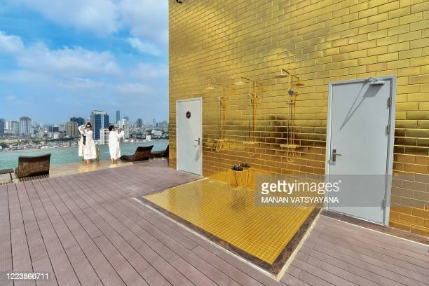 Guests pose for selfies at the infinity pool of the newlyinaugurated Dolce Hanoi Golden Lake hotel the world's first goldplated hotel in Hanoi on...