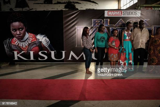Guests pose in front of an image of Kenyan actress Lupita Nyong'o before the African premier of the Marvel film 'Black Panther' in Kisumu Kenya on...