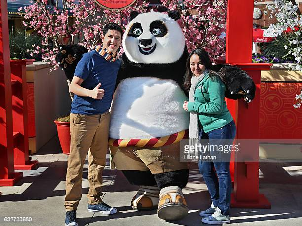 Guests pose with Po from the 'Kung Fu Panda' film series at Universal Studios Hollywood on January 25 2017 in Universal City California