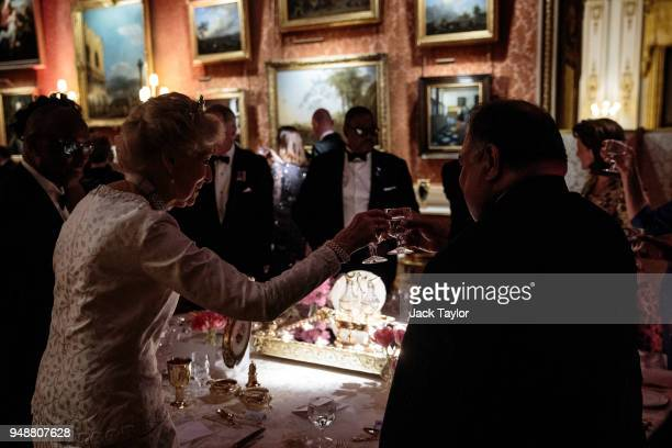 Guests raise their glasses during speeches as they attend the Queen's Dinner at Buckingham Palace in the week of the 'Commonwealth Heads of...