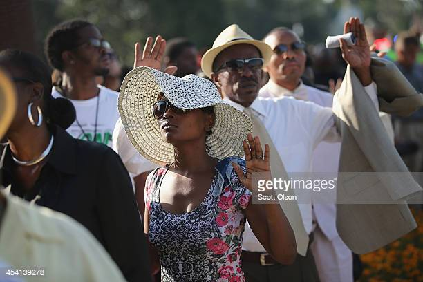 Guests raise their hands as they wait in line to enter the Friendly Temple Missionary Baptist Church for the funeral of Michael Brown on August 25...