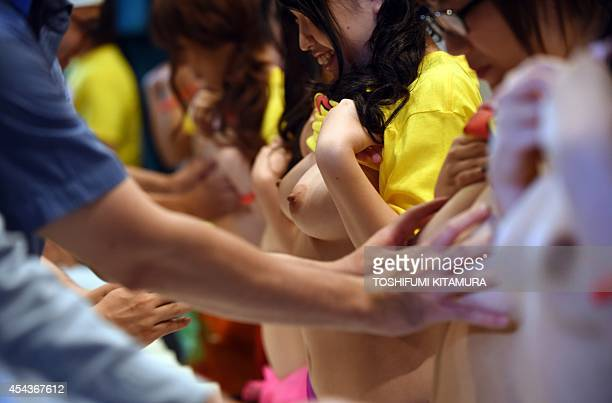 Guests reach towards the breasts of nine Japanese porn actresses in Tokyo on August 30 during a charity event loosely translated as 'Boob Aid' The...