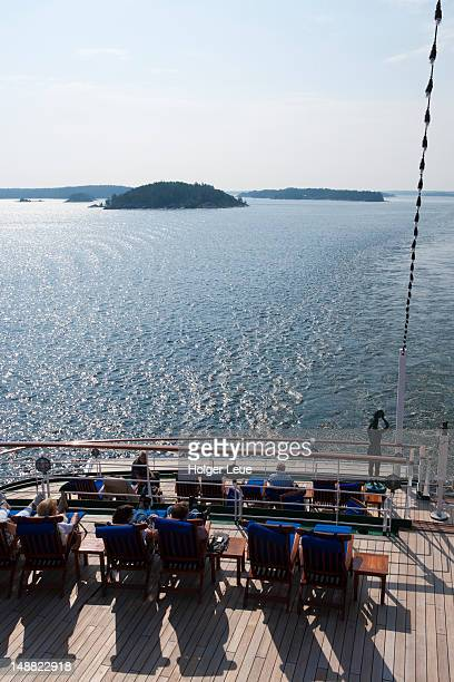 Guests relaxing on deck as cruise ship MS Deutschland passes through Stockholm archipelago, near Stockholm.