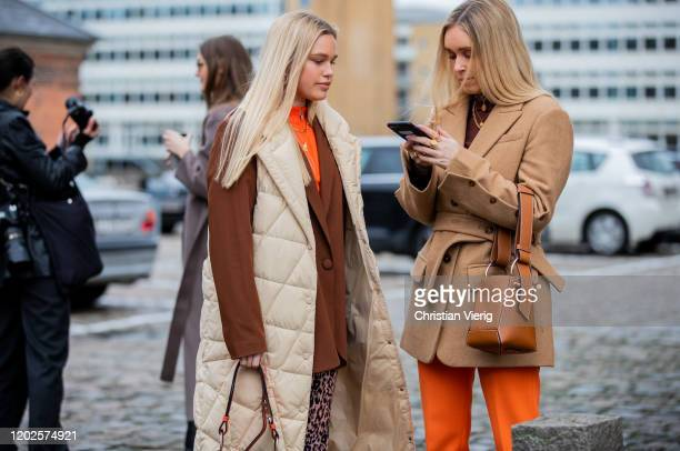 Guests seen wearing beige belted jacket and a guest wearing brown blazer sleeveless vest orange pants brown bag outside Mykke Hofmann on Day 1 during...