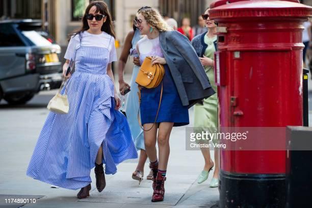 Guests seen wearing blue striped dress outside David Koma during London Fashion Week September 2019 on September 15, 2019 in London, England.