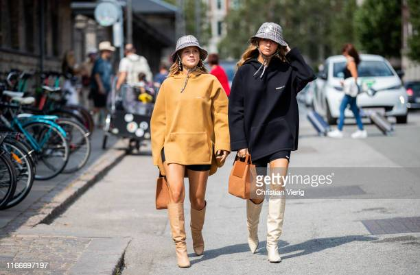 Guests seen wearing bucket hat and hoody brown bag boots outside Holzweiler during Copenhagen Fashion Week Spring/Summer 2020 on August 07 2019 in...
