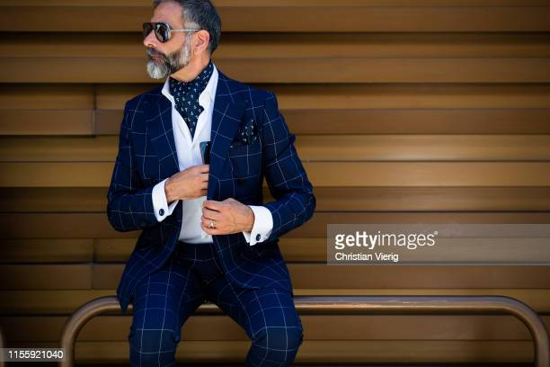Guests seen wearing plaid navy suit during Pitti Immagine Uomo 96 on June 13, 2019 in Florence, Italy.