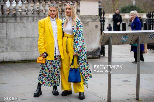 Guests seen wearing skirt and coat with floral print, yellow pants, blazer, bag outside Shrimps during London Fashion Week February 2020 on February...