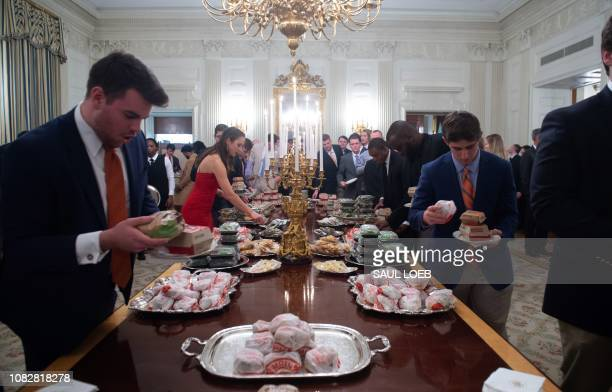 Guests select fast food that the US president purchased for a ceremony honoring the 2018 College Football Playoff National Champion Clemson Tigers in...