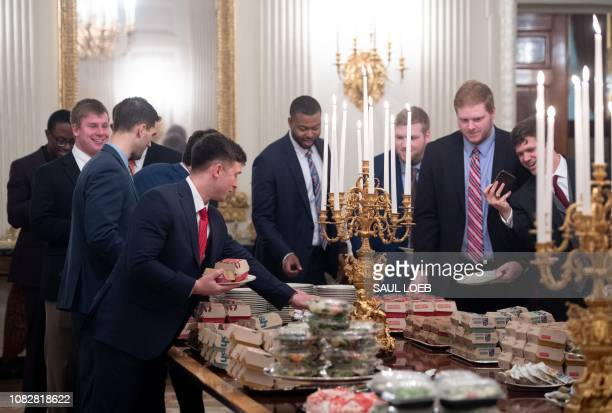 TOPSHOT Guests select fast food that the US president purchased for a ceremony honoring the 2018 College Football Playoff National Champion Clemson...