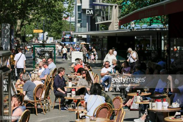 Guests sit on the outside terrace in front of a restaurant on the second day that people are no longer required to show a negative Covid test result...