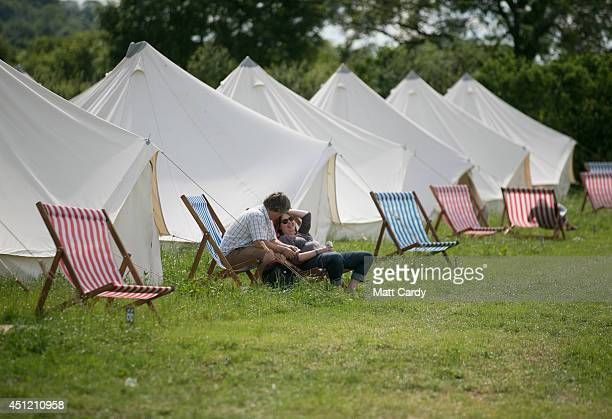 Guests sit outside their bell tent at the PopUp Hotel which offers festival goers alternative luxury camping close to the Glastonbury Festival site...