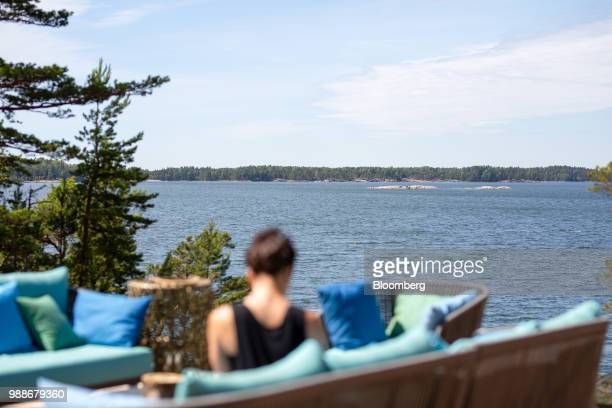 Guests sits on a terrace looking out to the Baltic sea on SuperShe island near Raasepori, Finland, on Wednesday, June 27, 2018. The price of...