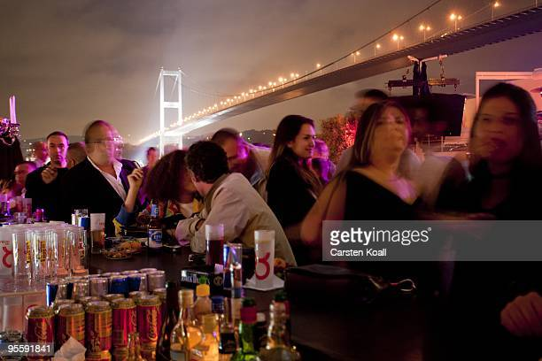 Guests spend the evening in the club Reina at the shoreline of the Bosporus and under the Bosporus Bridge in the district Ortakoyon May 27 2005 in...