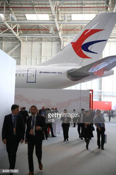 Guests stand around the Airbus A330 plane during the inauguration ceremony of the Airbus Long Range Cabin Completion Centre in Tianjin on September...