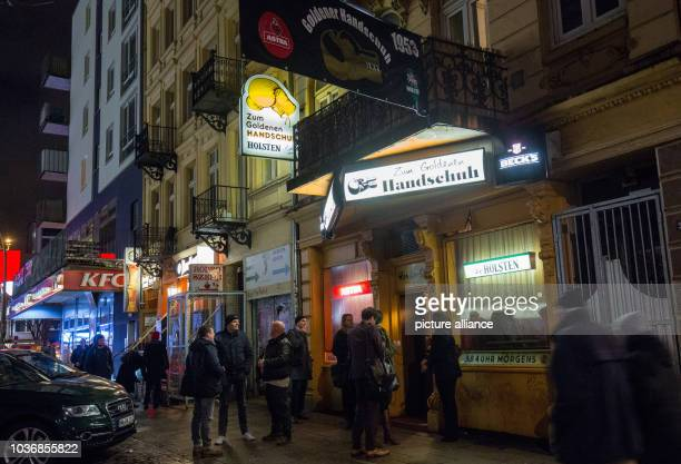 Guests stand in front of the 'Zum goldenen Hanschuh' pub ahead of a book presentation from author Heinz Strunk in Hamburg Germany 23 February 2016...