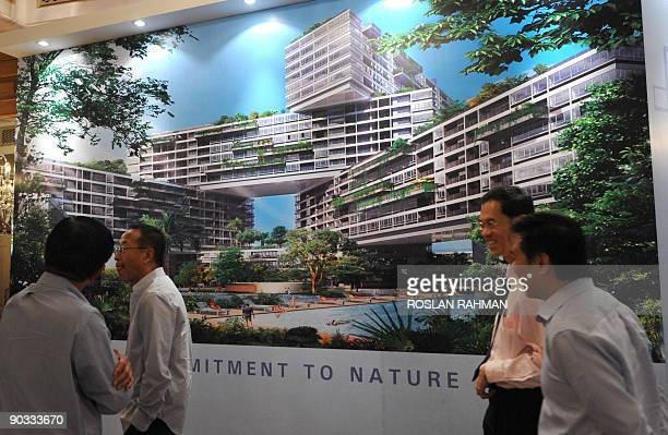 Guests stand infront an illustration of an upscale condominium development in Singapore during a preview on September 4 2009 by developer CapitaLand...